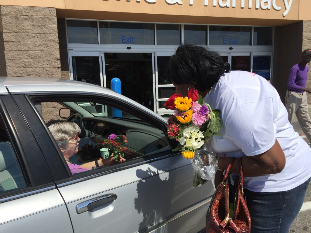 Mary Bethune, Katrina Collins' daughter, passes out flowers to strangers in the Walmart Roebuck parking lot. (Photo by: Chanda Temple)
